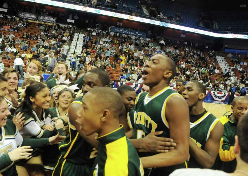 The Trinity Catholic boys basketball team celebrates their 57-51 win over Career Magnet in the Class M state championship game at Mohegan Sun Arena in Uncasville, Conn., March 19, 2011.