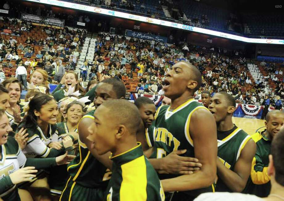 The Trinity Catholic boys basketball team celebrates their 57-51 win over Career Magnet in the Class M state championship game at Mohegan Sun Arena in Uncasville, Conn., March 19, 2011. Photo: Kathleen O'Rourke / Stamford Advocate