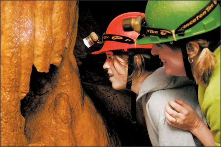 """Anne Mullens, right, and her daughter Kate Baldrey look into the mouth of the """"monster"""" in the 1,270-foot-long Riverbend Cave, which lies in a limestone belt between 475 and 820 feet above sea level. Photo: Simon Capet/Special To The Seattle P-I"""