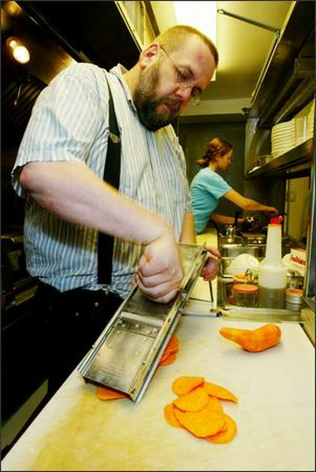 Hot Dish co-owner and chef Daniel McGlothlen slices yam chips as Charlotte Elliott, line cook, works in the background. Photo: Grant M. Haller/Seattle Post-Intelligencer