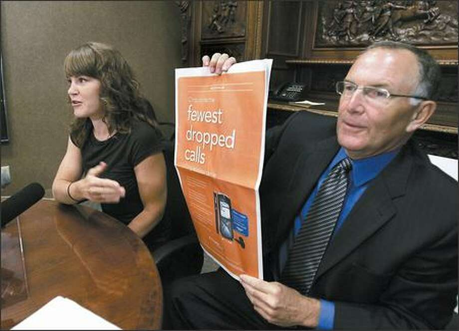 Seattle lawyer Mike Withey displays a Cingular Wireless ad Thursday as he and his client, Amy Frerker, announce the filing of a federal lawsuit alleging poor service to AT&T Wireless users. Photo: / Associated Press