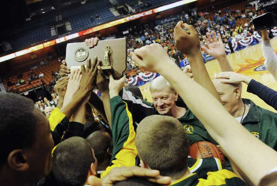 Coach Mike Walsh and the Trinity Catholic boys basketball team celebrate their 57-51 win over Career Magnet in the Class M state championship game at Mohegan Sun Arena in Uncasville, Conn., March 19, 2011. Photo: Kathleen O'Rourke / Stamford Advocate