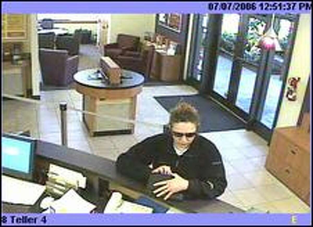 Attila the Bun Bandit -- she wears her hair in a bun -- seen in action. The immaculately groomed bank robber carries a makeup bag for her loot.