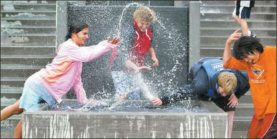 Liana Merrill, Tyler Campbell, Jeff Sargent and Jonathan Ryan have fun with the new fountains installed on Bremerton's redeveloped waterfront. The teens are in a sailing class at the Bremerton Yacht Club and sailed to downtown Bremerton's new marina for lunch. They were already wet from the rainy sail. Photo: Paul Joseph Brown/Seattle Post-Intelligencer