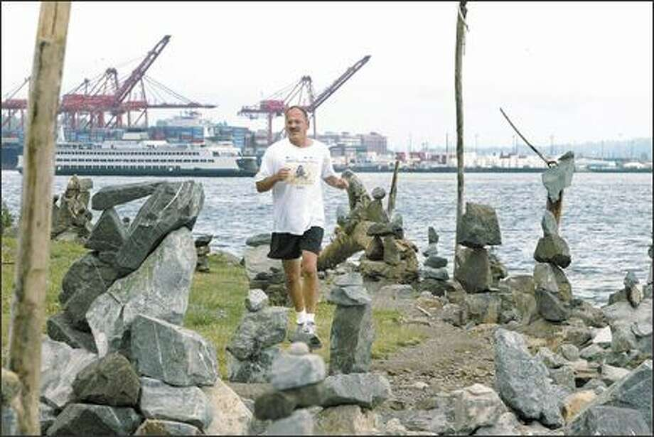 Kevin Fox runs past sculptures of stacked rocks and driftwood Wednesday at Myrtle Edwards Park. A homeless man, called Stacker by friends, uses what nature provides to create his art. Photo: Grant M. Haller/Seattle Post-Intelligencer