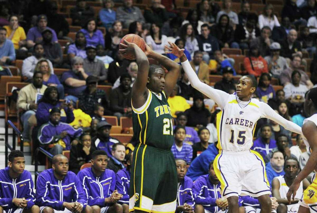 Trinity Catholic's Aaron Spence controls the ball against Career Magnet's Kenneth Armstead in the boys basketball Class M state championship game at Mohegan Sun Arena in Uncasville, Conn., March 19, 2011. Trinity won 57-51.
