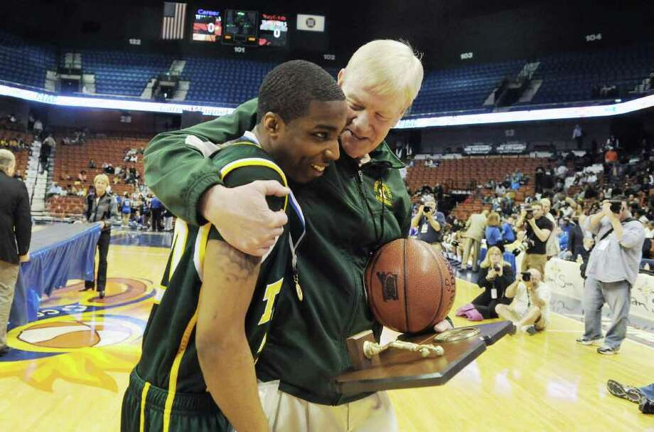 Trinity Catholic head coach Mike Walsh celebrate with Jonathan Boykin after their 57-51 win over Career Magnet in the Class M boys basketball state championship game at Mohegan Sun Arena in Uncasville, Conn., March 19, 2011. Photo: Kathleen O'Rourke / Stamford Advocate