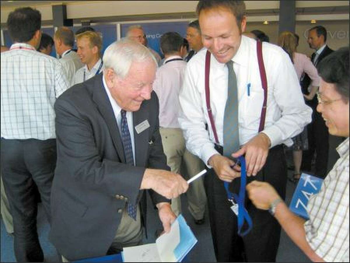 Joe Sutter signs copies of his book for reporters during a Boeing reception at the air show. Sutter led the Boeing engineering team in the 1960s that designed and developed the 747-100.