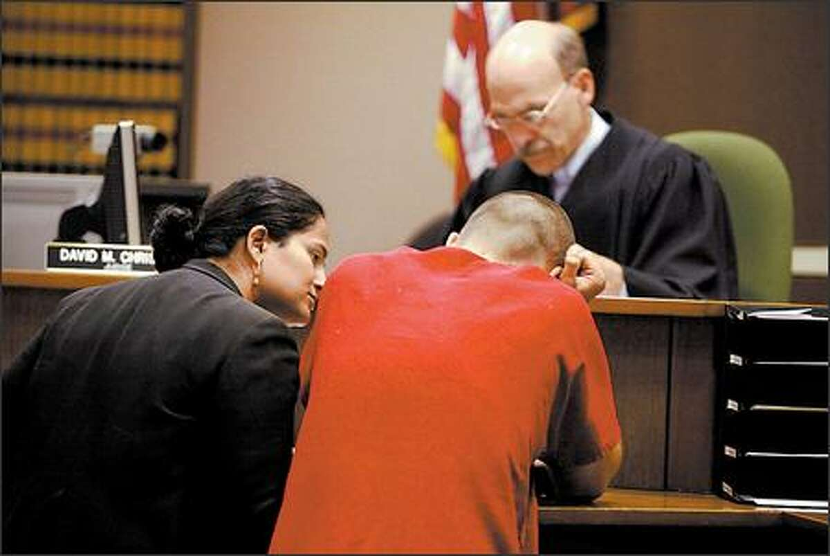 Public Defender Kuljinder Dillon, left, talks to the suspect in the Skyway shootings during his first court appearance in Kent on Friday. Judge David Christie set bail at $1 million.