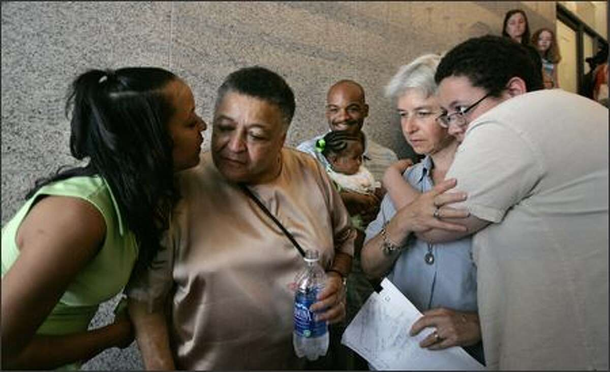 Nicole Baker, left, kisses her mother, Barbara Steele, as her other mother, Beth Reis, second from right, is hugged by granddaughter Suzette Verzola while they wait for a news conference to begin in Seattle. Steele and Reis were plaintiffs in a court case challenging a ban on same-sex marriage in the state. At center, grandson Joseph McCommons-White holds the couple's granddaughter, Naomi Baker. The state Supreme Court upheld the ban on gay marriage Wednesday. (AP Photo/Elaine Thompson)