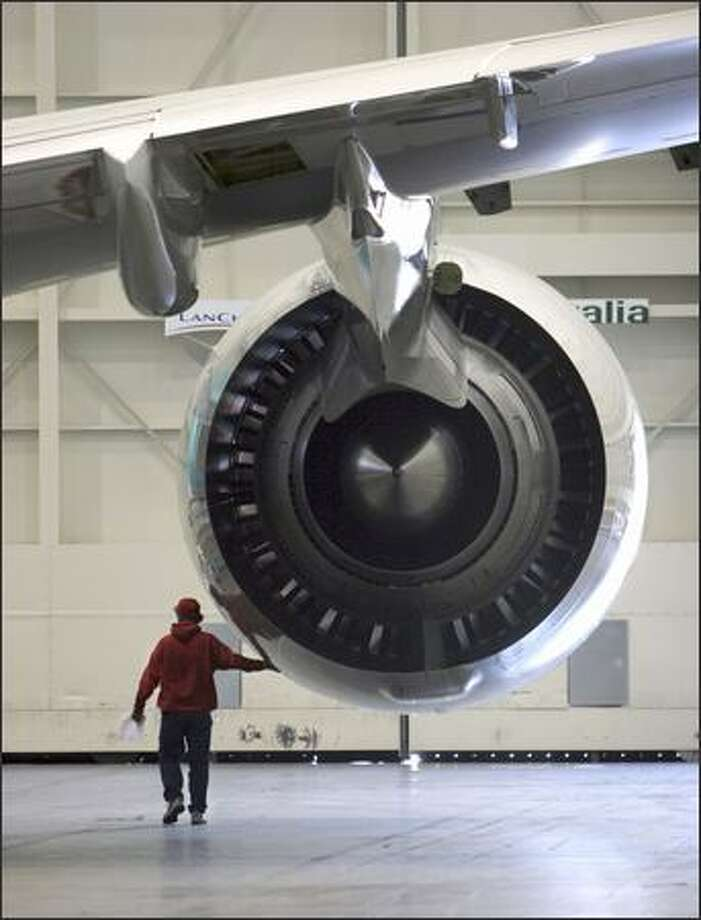A worker walks past the jet engine of a Boeing 777 at the Boeing plant in Everett, where the Boeing 747, 767, 777 commercial jets are assembled, and where the 787 Dreamliner will be built. Photo: / Bloomberg News