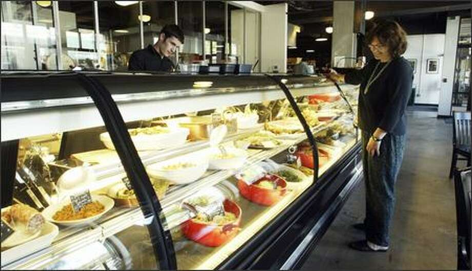 A customer peruses Porcella's high-end deli case, which has meals to go, from house-cured meats to escargots bourguignonne to fancy side salads. Photo: Gilbert W. Arias/Seattle Post-Intelligencer