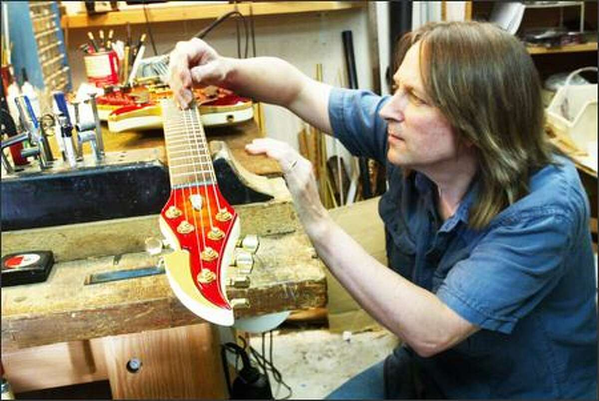 Brian Nelson adjusts the intonation on an FM Centauri he built in his basement workshop in Seattle. His list of big-time clients for his custom-made guitars once included Nirvana, Soundgarden and Pearl Jam.