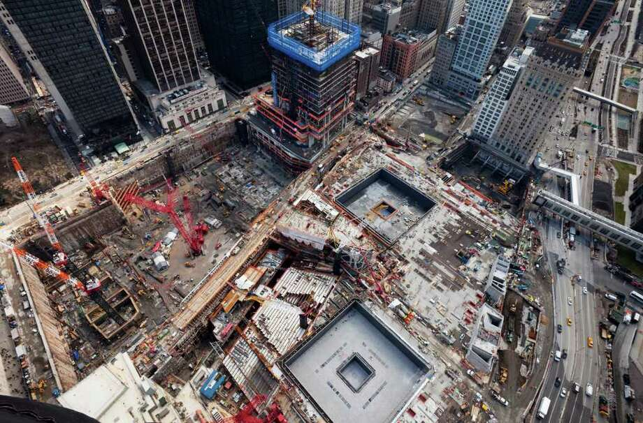 This March 11, 2011 photo shows the World Trade Center site in New York. Rebirth has been slow in coming to ground zero, but with six months remaining until the first portions of the national 9/11 memorial are scheduled to open to the public, the work to turn a mountain of rubble into one of the worldís great urban centers is thundering forward and beginning to produce some of the inspiring monuments designers envisioned nearly a decade ago.  The square outlines of the 9/11 Memorial and the rising steel structure of 4WTC, top center, are among visible signs of progress at the site. (AP Photo/Mark Lennihan) Photo: AP