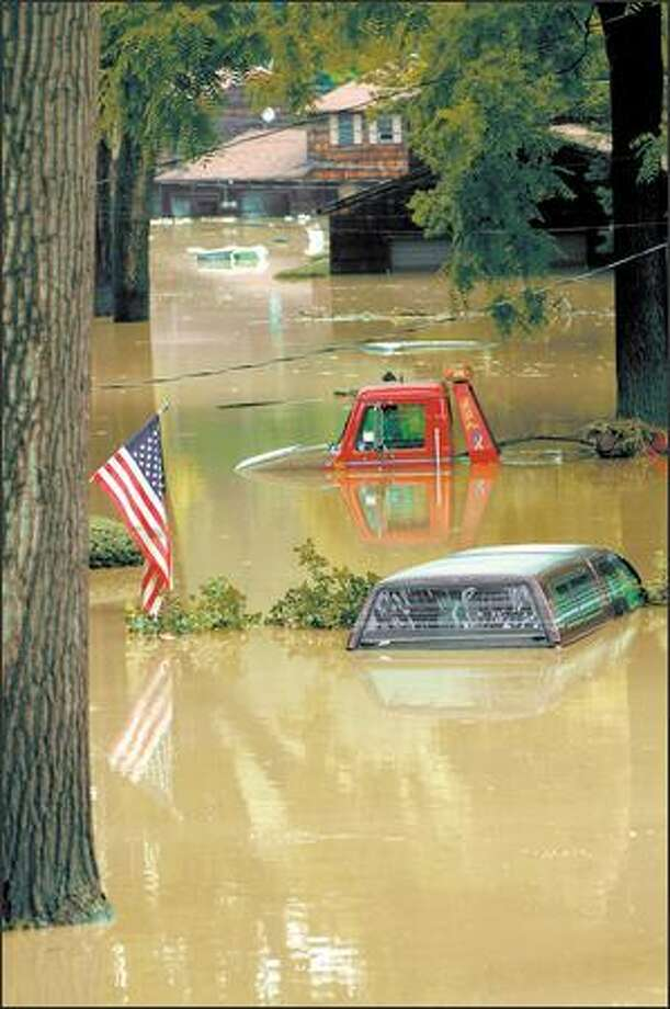 The Grand River was 11 feet above flood level early Friday, swamping property and prompting the evacuation of residents. Photo: / Associated Press