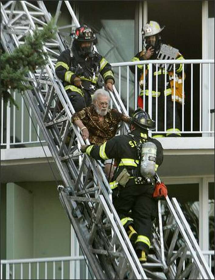 Seattle firefighters help an elderly man descend a rescue ladder during a fire at the Four Freedoms House apartment building in North Seattle.  One elderly resident died. Photo: Dan DeLong/Seattle Post-Intelligencer