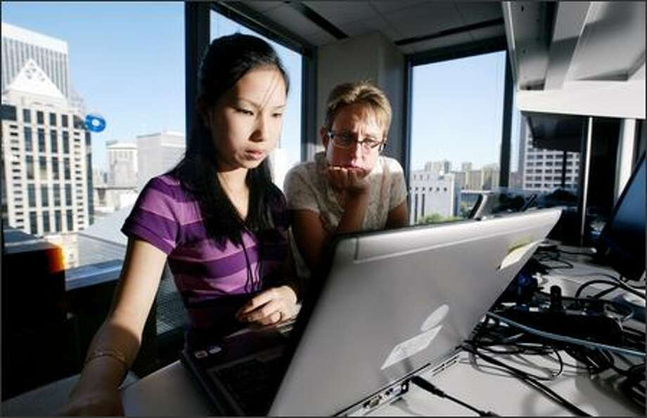 Intern Thai Hang Nguyen, 17, is assisted by supervisor Alice Heartgrove, a PC analyst, in the information systems department at Preston Gates & Ellis in Seattle Photo: Dan DeLong/Seattle Post-Intelligencer
