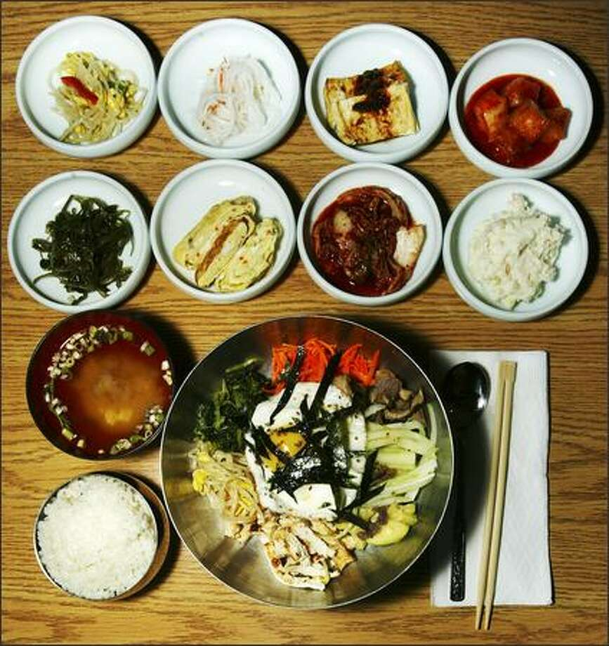 Four Seasons Korean Restaurant offerings include bibimbob, bottom, with julienne carrots, bean sprouts, beef, egg and rice, along with eight appetizers and a bowl of miso soup. Photo: Grant M. Haller/Seattle Post-Intelligencer