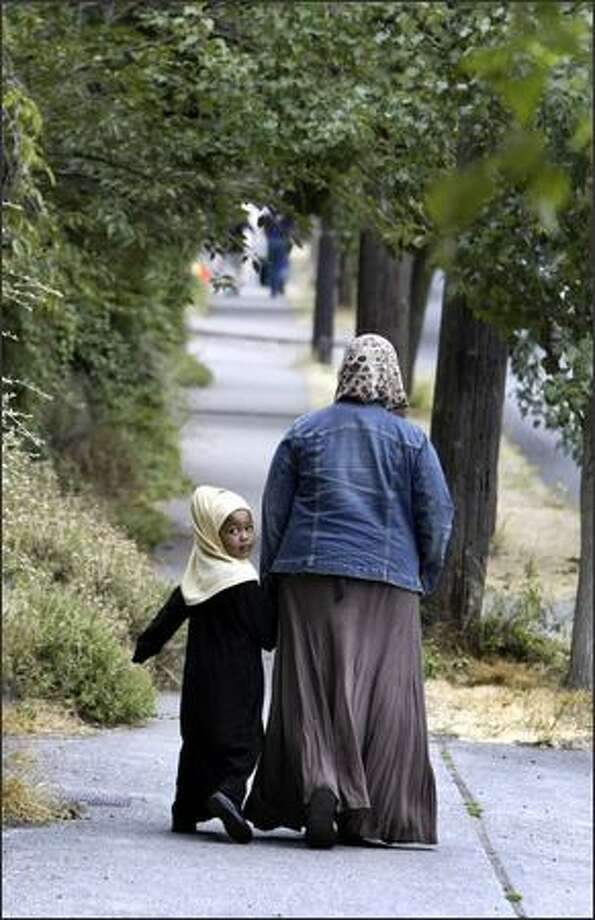 A girl looks back at spectators as she walks to the Idriss Mosque Friday with her mother before the peace march. Photo: Gilbert W. Arias/Seattle Post-Intelligencer