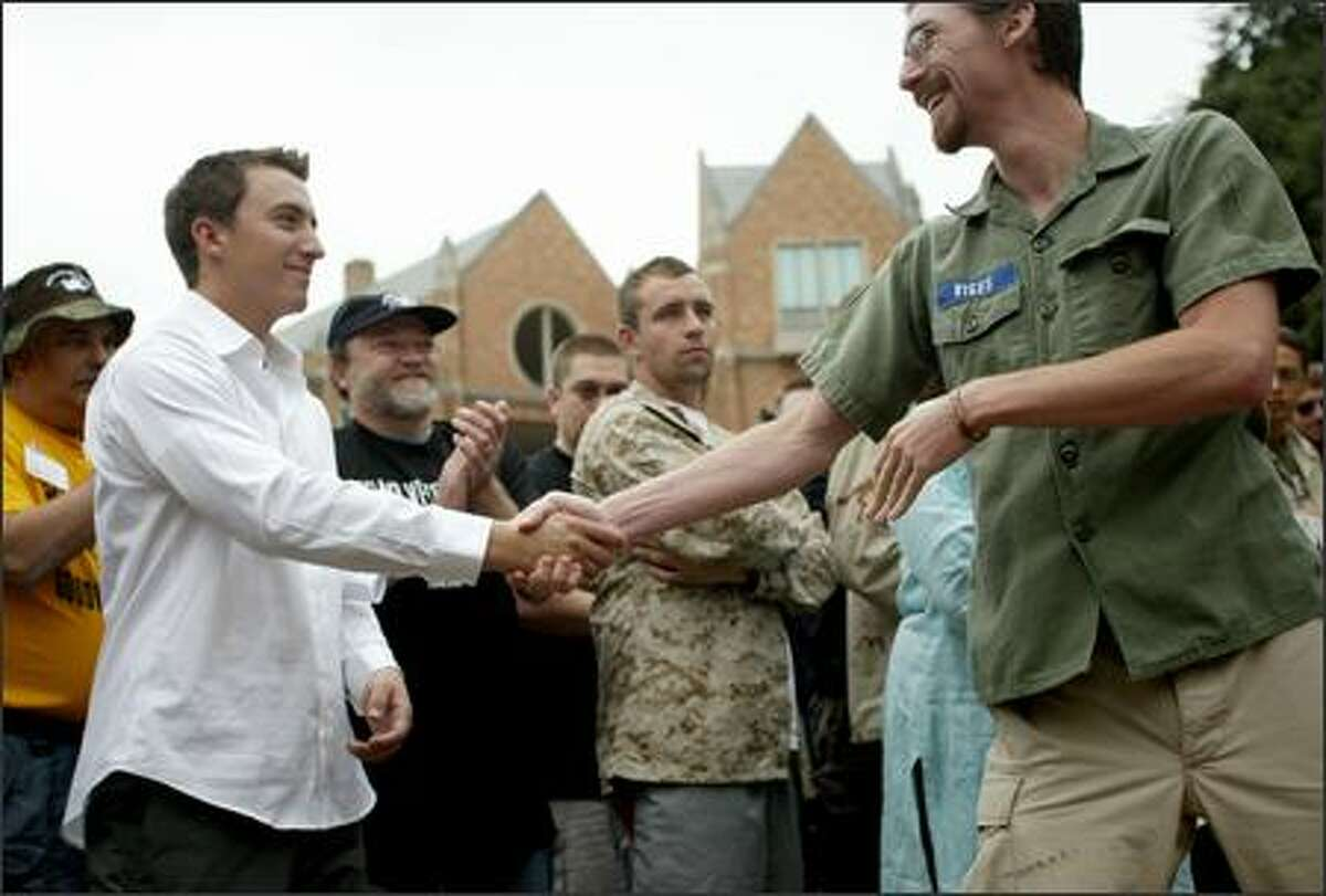 Army Sgt. Ricky Clousing, left, shakes hands with Iraq war veteran Benjamin Viges, a conscientious objector, Friday on the University of Washington campus during a national Veterans for Peace convention. Clousing was an interrogator during his time in Iraq and said some of what he witnessed drove his decision to desert from the Army. Clousing surrendered Friday night to military authorities.