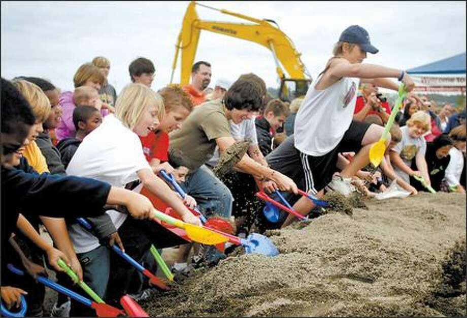 Youngsters armed with plastic shovels break ground Tuesday at the site of The Landing, which is near Fry's Electronics in Renton. Prizes were buried in the sand. Photo: Joshua Trujillo/Seattle Post-Intelligencer