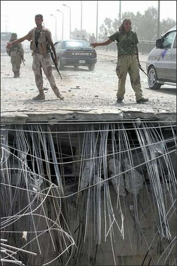 Iraqi police in Baghdad direct traffic next to a crater on a bridge Tuesday. The crater was left by a car bombing hours earlier. Photo: / Associated Press