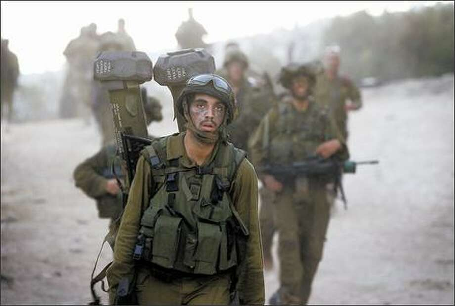 Weary Israeli soldiers arrive at the border as they return to northern Israel from Lebanon on Tuesday. Israel lost at least 118 soldiers during the 34-day fight between its army and Hezbollah militants. Photo: / Associated Press