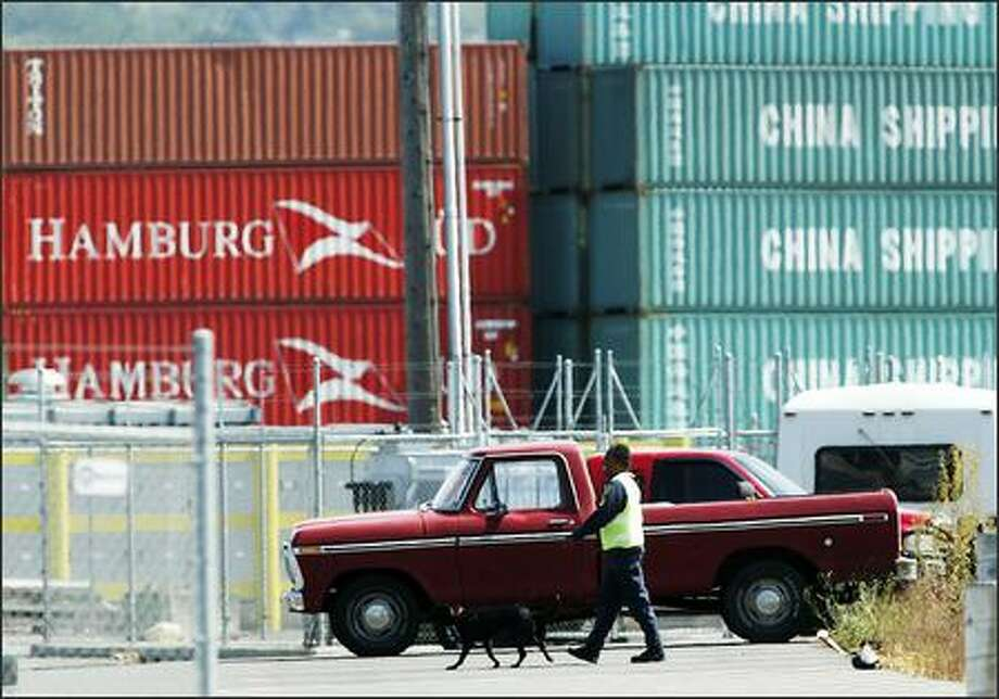 "A port officer and a dog walk the area around Terminal 18 as authorities check containers after ""anomalies"" were found during an inspection of two containers that originated in Pakistan. Dozens of workers were evacuated as the terminal was locked down. Photo: SCOTT EKLUND/P-I"