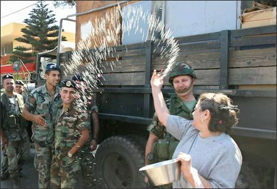 A Lebanese woman throws rice and rose petals at Lebanese soldiers Thursday after their arrival to the town of Marjayoun in line with a U.N. cease-fire plan to end fighting between Israel and Hezbollah. Photo: / Associated Press