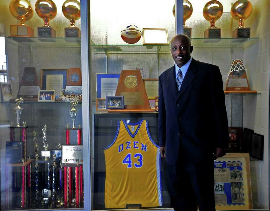 Head basketball coach, Andre Boutte poses in front of the trophy case in the gym at Ozen High School in Beaumont, Saturday. Tammy McKinley/The Enterprise Photo: TAMMY MCKINLEY / Beaumont