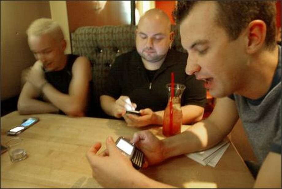 "Joe Wilson, left, Kyle Johnson and Brian Westbrook use their cell phones to ""check in"" with the Dodgeball mobile social networking service. Photo: Mike Urban/Seattle Post-Intelligencer"