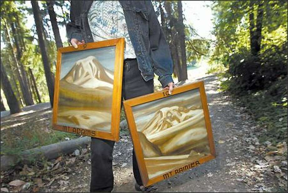 Sheila Brown, education supervisor at Camp Long, holds up paintings made by founder Clark Schurman, which will be on display Saturday and Sunday at the Arts in Nature Festival. Photo: Karen Ducey/Seattle Post-Intelligencer