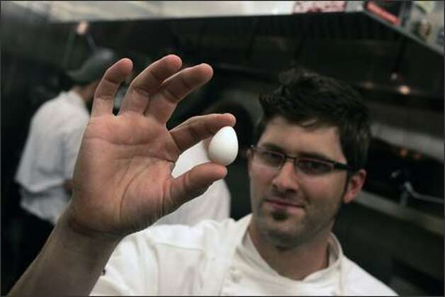 "Chef Tyler Palagi displays a Bobwhite quail egg in his kitchen at Ferrara Ristorante. ""The quail egg takes just two to three minutes to hard cook,"" he says. Photo: MIKE KANE/P-I"