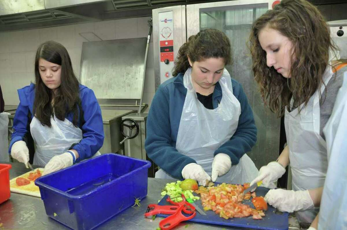 Left to right are Bi-Cultural students Mira Schildkraut, Elizabeth Milstein and Hannah Tisser working at a soup kitchen in Jerusalem to help prepare fresh meals for delivery to the homebound and the soup kitchen's walk-in clients.