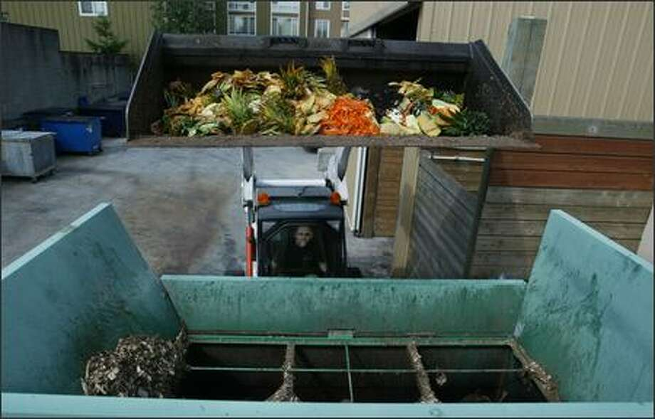Tyler Dierks of Seattle University dumps fruit and vegetable remains into a machine that mixes them with wood chips to form compost. Photo: Scott Eklund/Seattle Post-Intelligencer