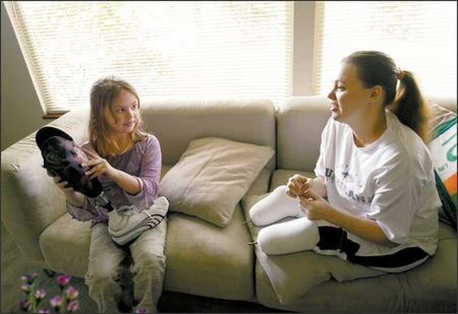 After returning home from school, Karma checks out her mother's new prosthetic legs in their Edmonds home. Karma helped Rose pick out the images of fairies that are laminated onto the legs. Photo: Dan DeLong/Seattle Post-Intelligencer