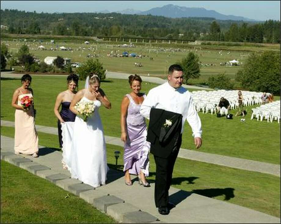 Groom Jim Lambro, followed by his mother, Julie Hunter; bride-to-be, Rachelle Stinde; Katrina Stinde, holding the bridal train; and the bride's mother, Bev Stinde, return from taking wedding pictures at Lord Hill Farms. A soccer tournament is in the background. Photo: Jim Bryant/Seattle Post-Intelligencer