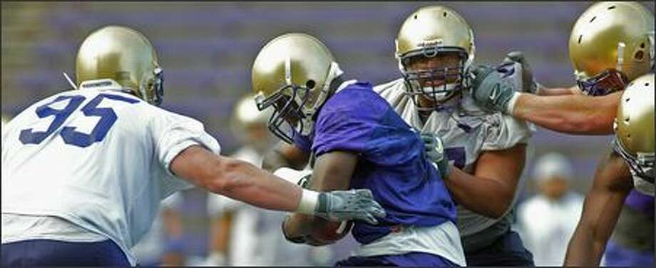 Backup defensive tackles Jordan Reffett (95) and Erick Lobos close in on running back Kenny James during the first day of practice. The defensive line has been revamped after a subpar 2005. Photo: Grant M. Haller/Seattle Post-Intelligencer