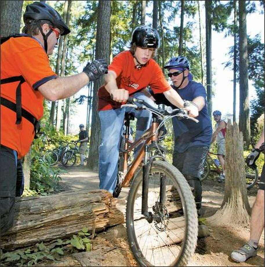 "Nicholas Connite gets a little help from Bob Hollander, right, as he practices going over a stack of logs on a trail during a Backcountry Bicycle Trails Club mountain biking ""boot camp."" Photo: KAREN DUCEY/P-I"