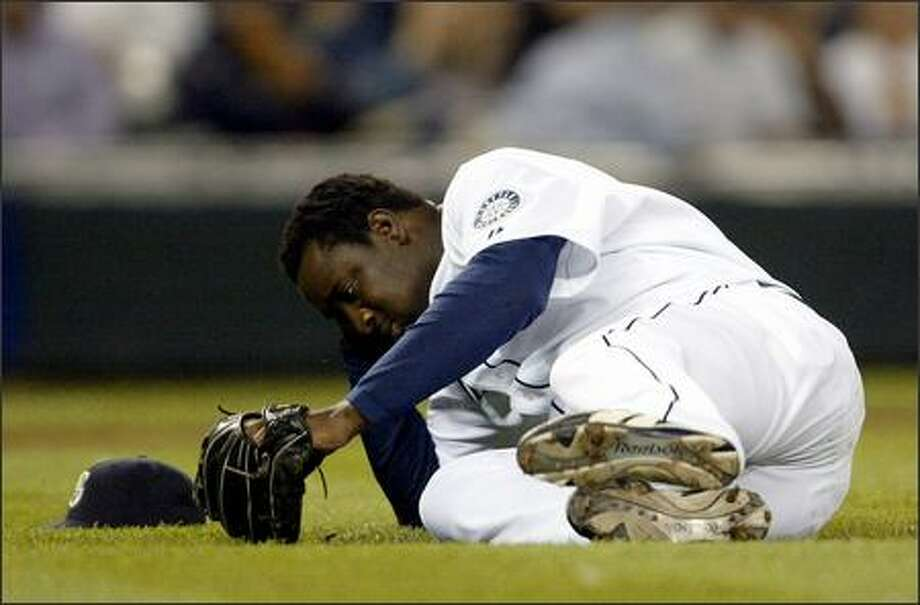 Mariners pitcher Rafael Soriano falls to the ground after taking a line drive to the head off of Los Angeles' Vladimir Guerrero during the eighth inning of play. Soriano was taken off the field on a stretcher and transported to the hospital. Photo: Mike Urban/Seattle Post-Intelligencer