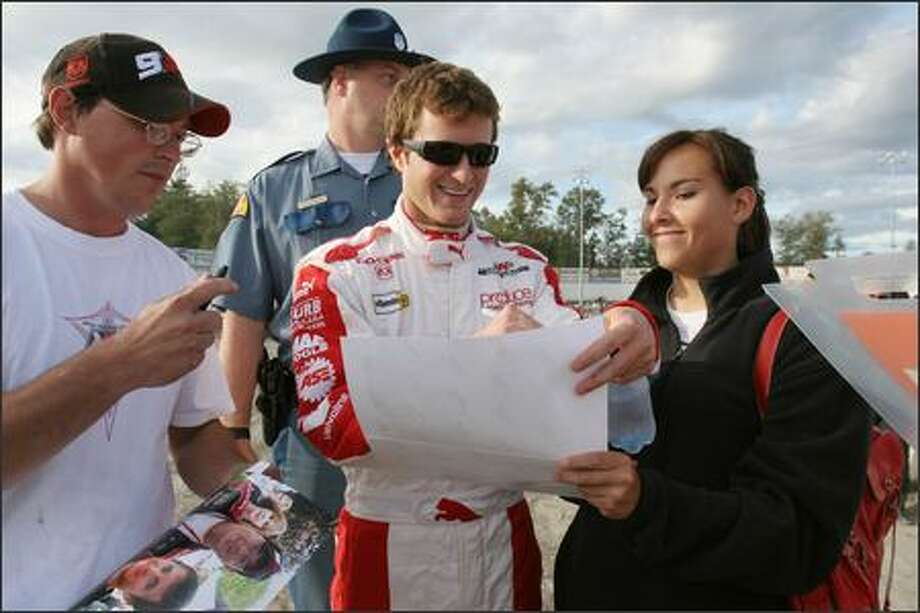 Kasey Kahne signs autographs for Joey Sparks of Sedro-Woolley, left, and Reba Guzman of Brewster. Photo: Meryl Schenker/Seattle Post-Intelligencer