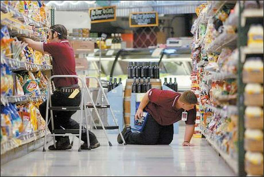 Jared Martin, left, and Steven Morgan, both working for RGIS, an inventory specialist company, take stock of shelves Thursday at Larry's Market on Queen Anne. Photo: Karen Ducey/Seattle Post-Intelligencer