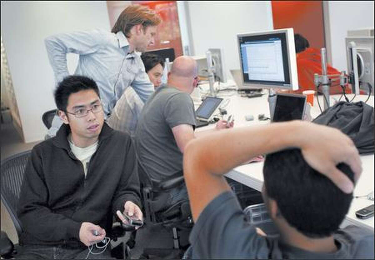 Designer Peter Chin discusses a smart phone with team leader Arthur Lam at a center where Microsoft engineers and designers work on hardware concepts for devices.