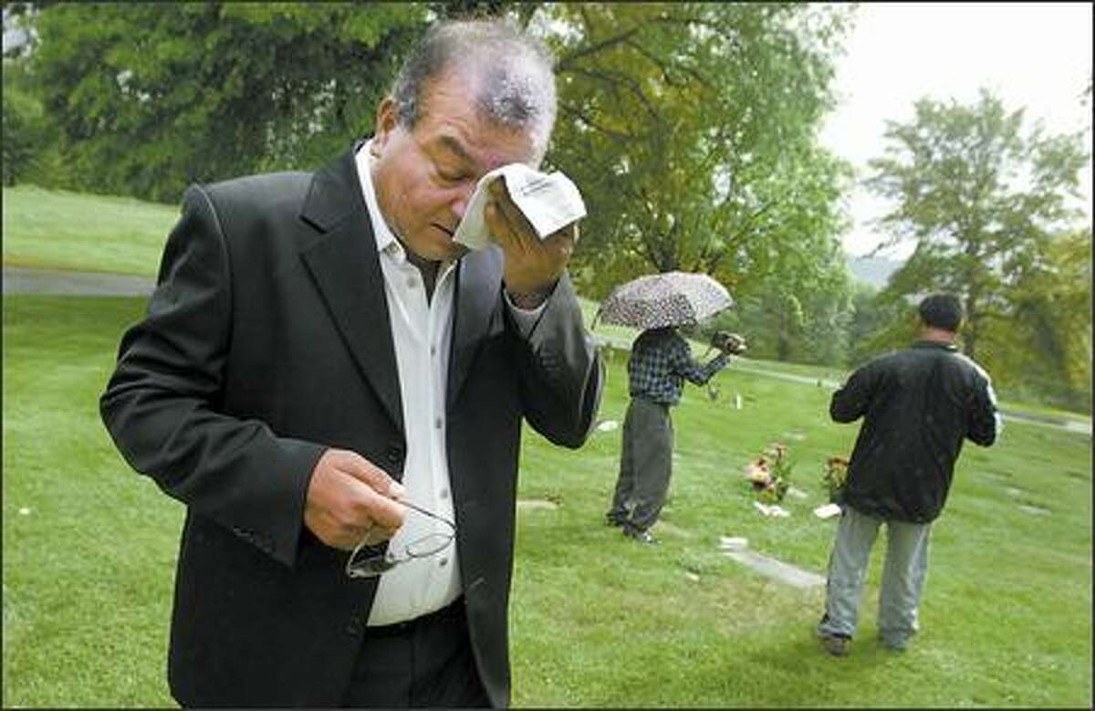 Jai Prasad wipes away tears as stands by two unmarked graves near Kelso on May 25, as two friends document his search for his sister.