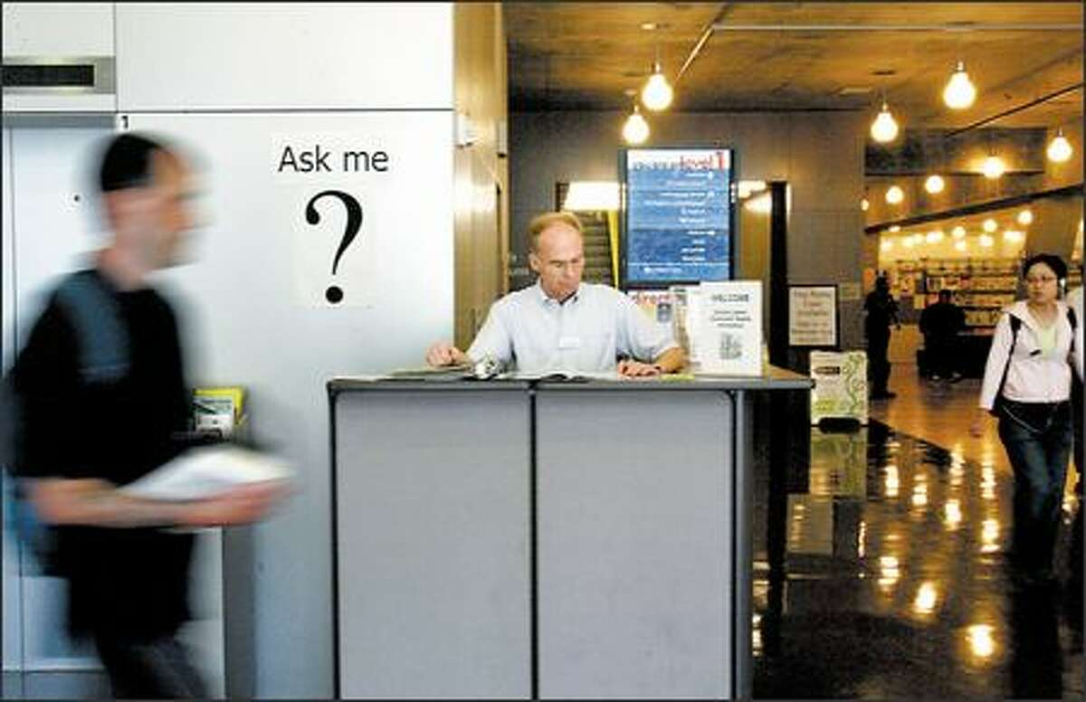 An employee staffs the temporary information booth at the downtown Central Library recently. People have found it difficult to navigate the impressive, $170 million building.