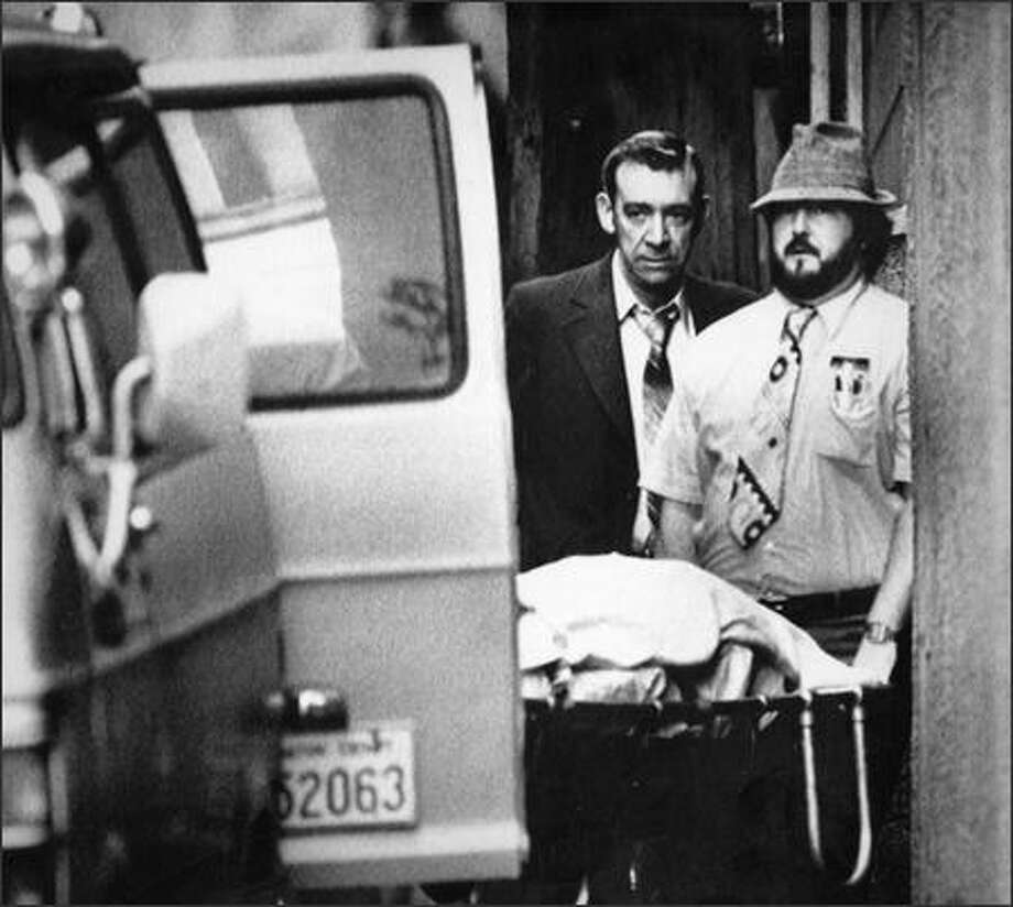 The body of one of 13 people found dead in February 1983 in a club in the International District is removed from the scene. Photo: / P-I File