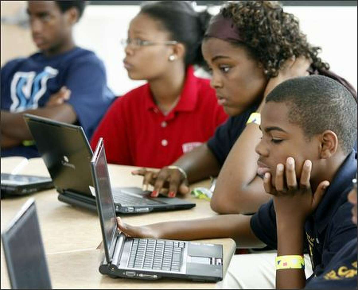 """Students use laptops on their first day at the Microsoft-designed """"School of the Future,"""" which opened its doors Thursday in a West Philadelphia neighborhood. The school, which took three years of planning, is being touted as unlike any in the world, with not only a high-tech building -- students have digital lockers and teachers use interactive """"smart boards"""" -- but also a learning process modeled on Microsoft's management techniques."""