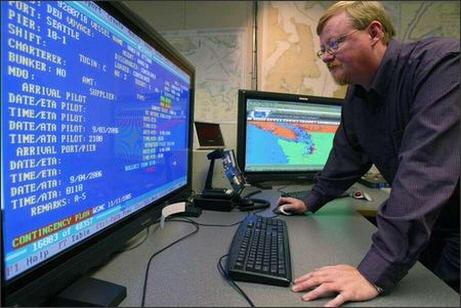 "John Bruno, operations manager at the Marine Exchange of Puget Sound, uses a system that ""pings"" vessels to track their movement. Photo: Paul Joseph Brown/Seattle Post-Intelligencer"