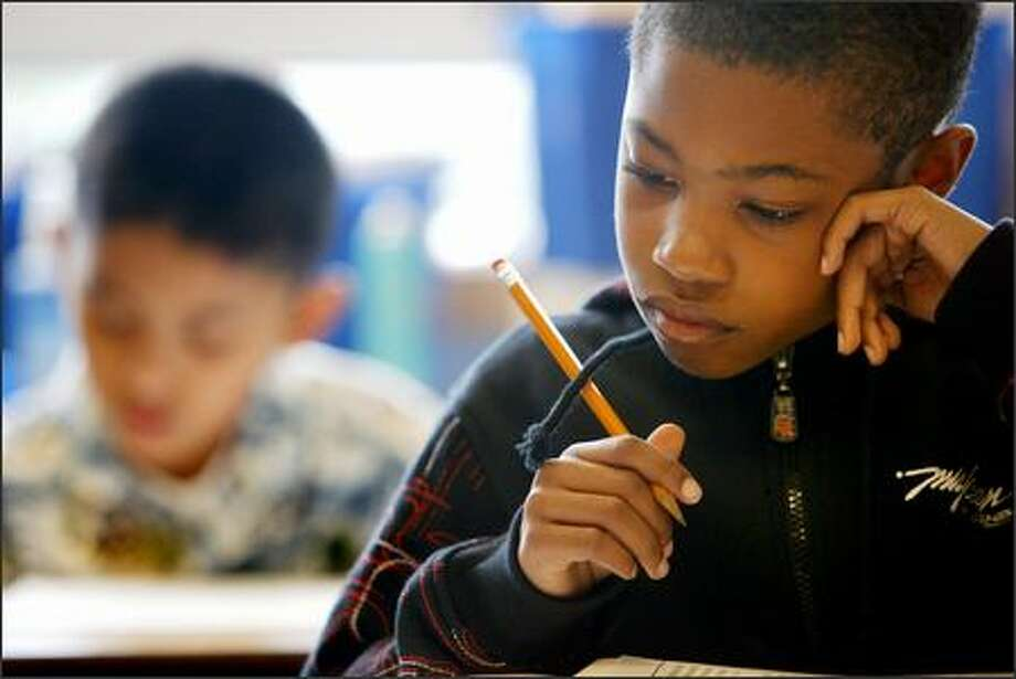 Fifth-graders Christian Collins, 11, front, and George Franada, 10, work on a reading assessment test Friday at John Muir Elementary. Photo: Dan DeLong/Seattle Post-Intelligencer