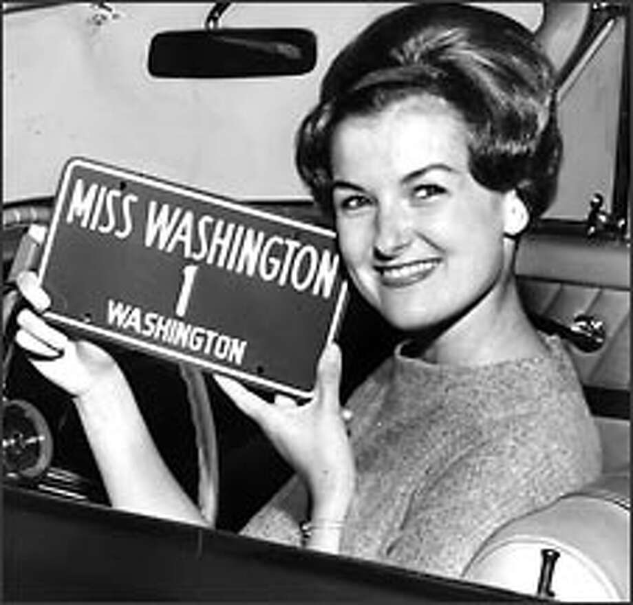 Gail Hannuk shows off the personalized license plate ordered for her by the governor after she won the Miss Washington title in 1961. Photo: P-I FILE/1961